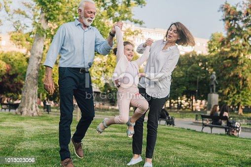 Senior couple having fun with grandchild