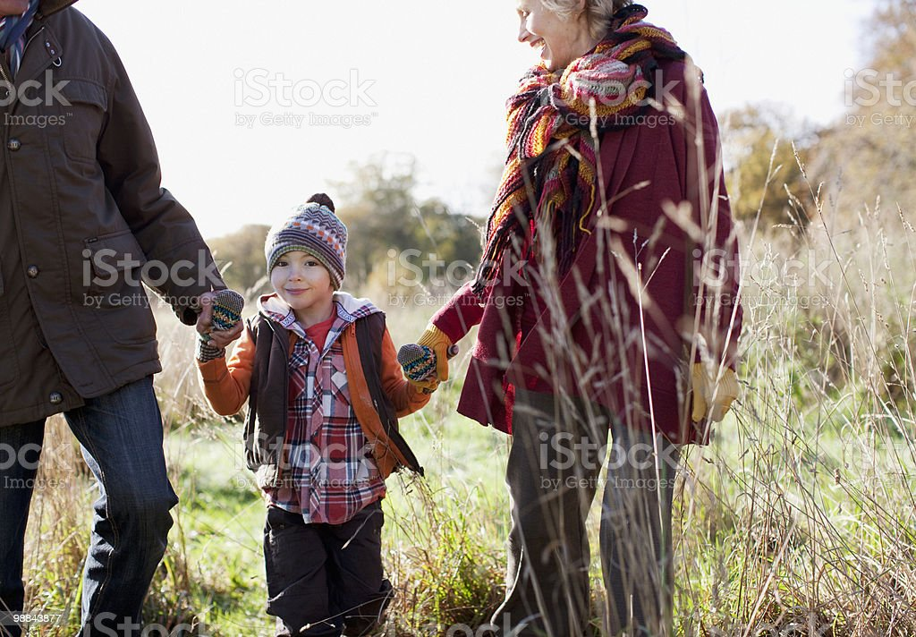 Grandparents holding hands with grandson outdoors royalty-free stock photo