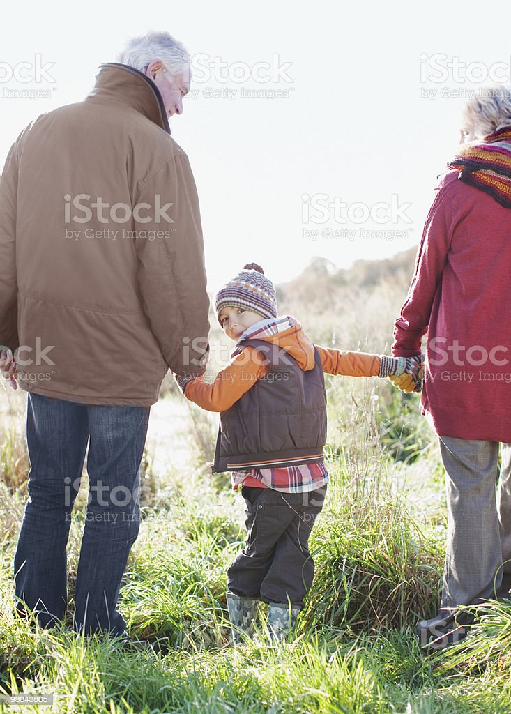 Grandparents holding hands with grandson royalty-free stock photo