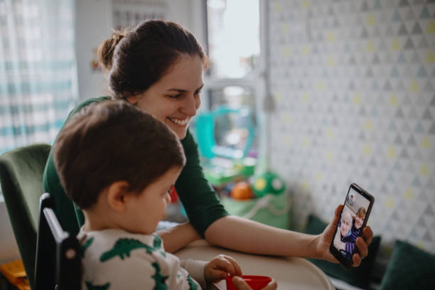 Grandparents in quarantine at home having video call with grandson and daughter stock photo