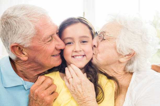 Grandparents kissing their granddaughter Grandparents kissing their granddaughter at home granddaughter stock pictures, royalty-free photos & images