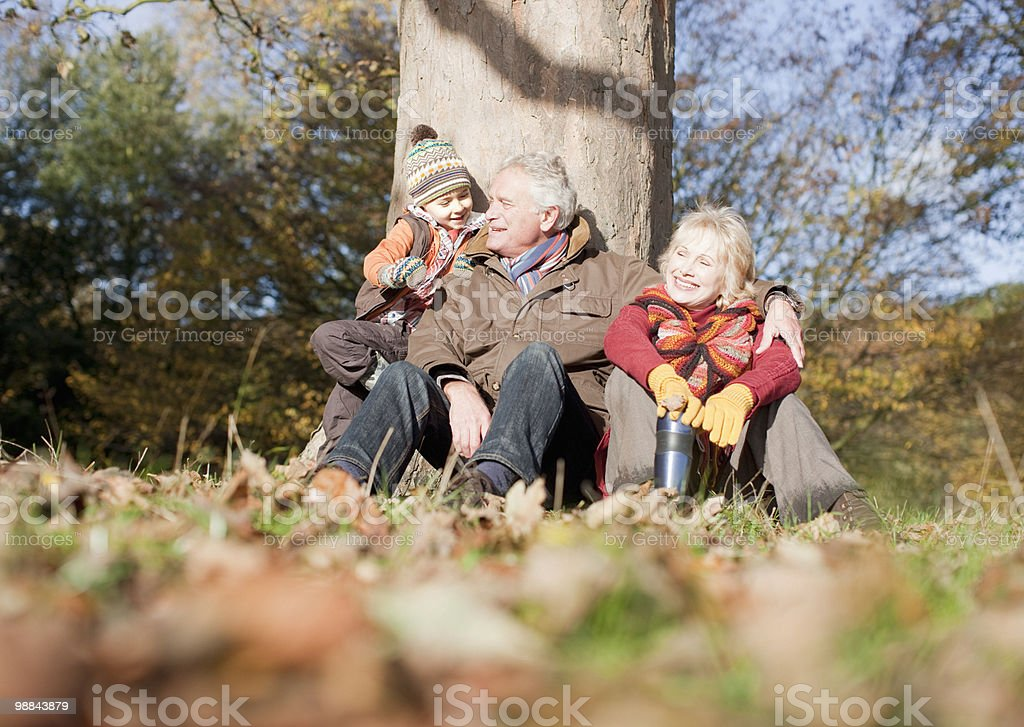 Grandparents leaning against tree with grandson royalty-free stock photo