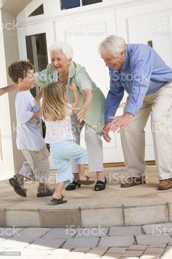 Grandparents meeting their grandchildren at the door royalty-free stock photo