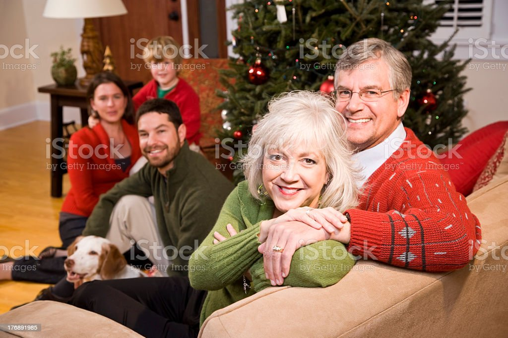 Grandparents on Christmas with family in background with dog royalty-free stock photo