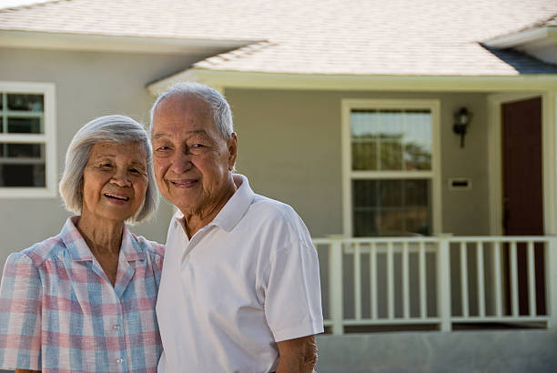 Grandparents - People Series Grandma and Grandpa in front of house smiling at the camera. filipino ethnicity stock pictures, royalty-free photos & images