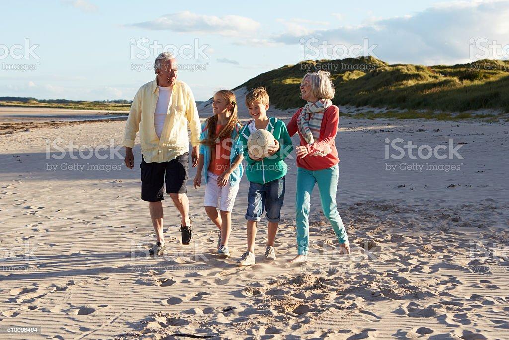 Abuelos jugando al fútbol con sus nietos en la playa - foto de stock