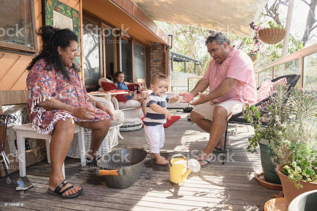 Großeltern mit Enkel auf Veranda vor Haus spielen – Foto