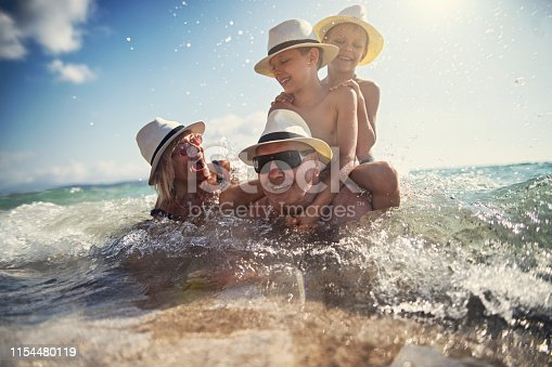 Little boys playing with their grandparents in the sea. The boys are riding grandfather and everybody is laughing. Nikon D850