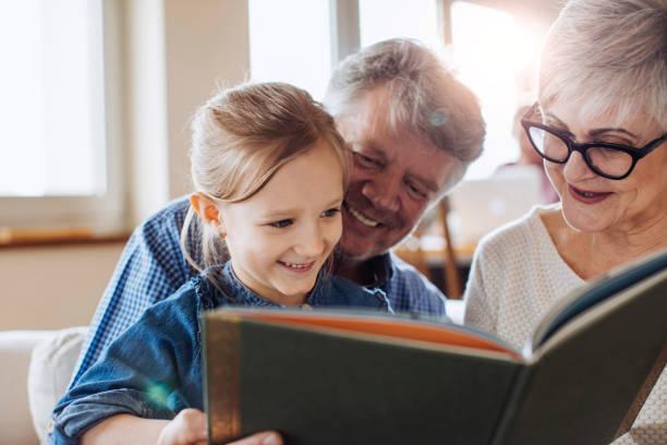 Lendo um livro para sua linda neta de avós - foto de acervo