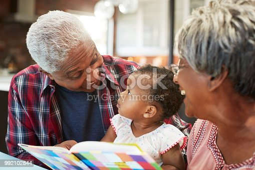 istock Grandparents Reading Book With Baby Granddaughter At Home 992102844