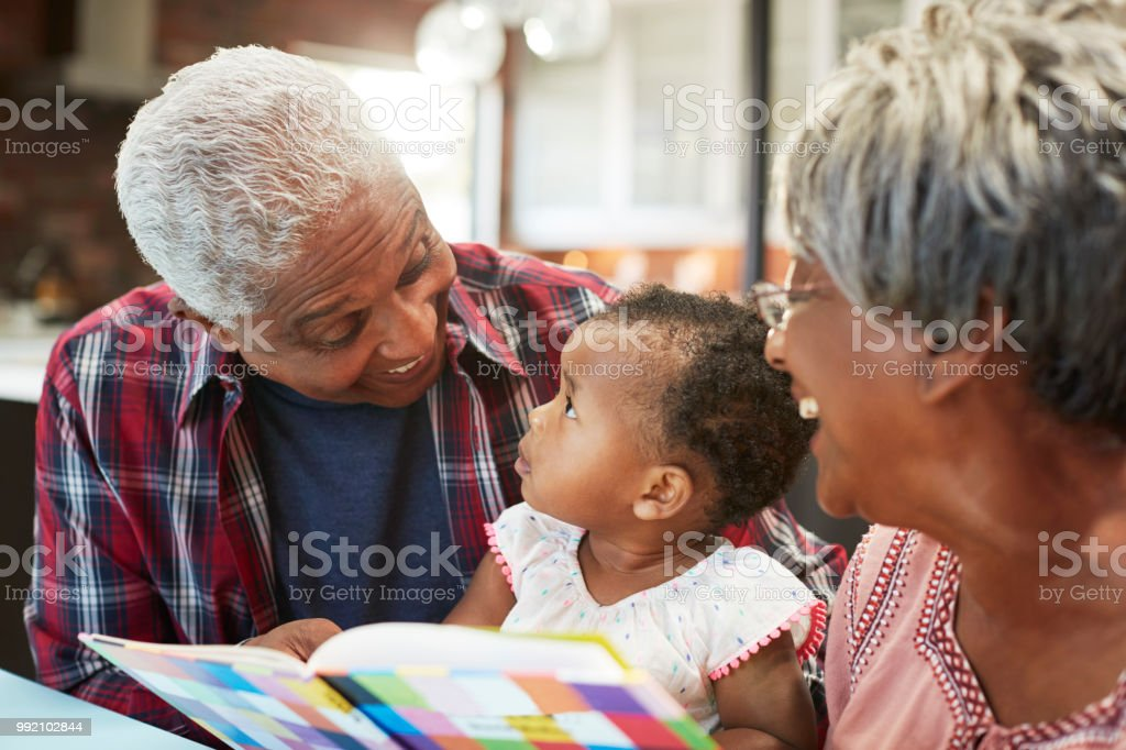 Grandparents Reading Book With Baby Granddaughter At Home stock photo