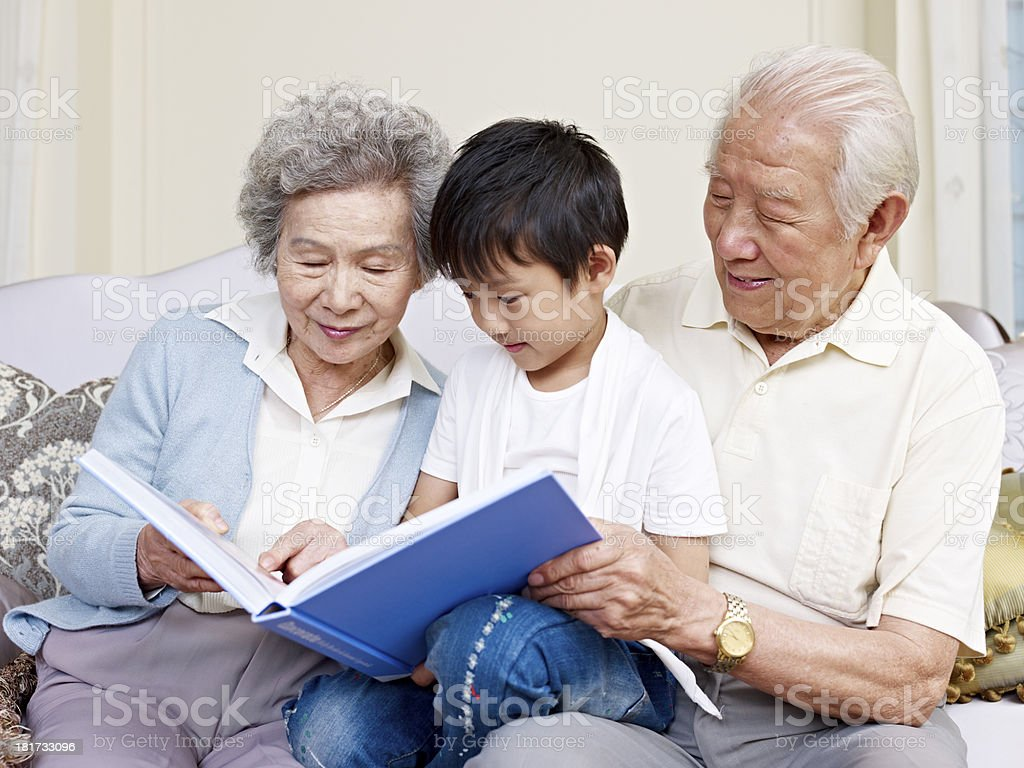 Grandparents reading to their grandson stock photo