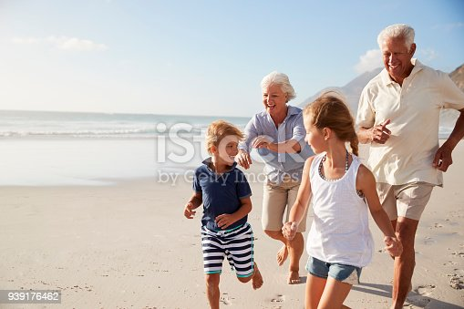 istock Grandparents Running Along Beach With Grandchildren On Summer Vacation 939176462
