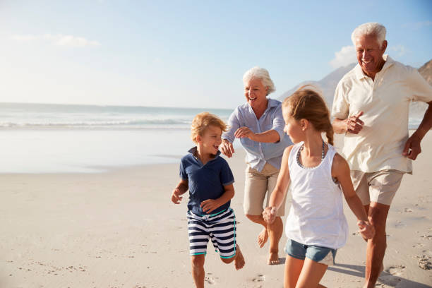 grandparents running along beach with grandchildren on summer vacation - retirement stock photos and pictures