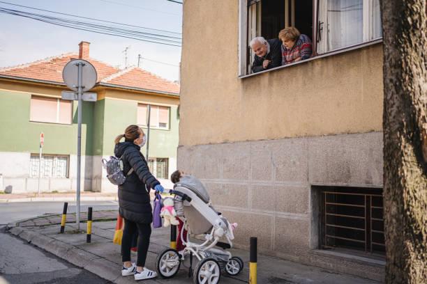 grootouders die hun grandaughters en dochter na één weeklockdown tijdens coronaviruspandemie zien - raam bezoek stockfoto's en -beelden