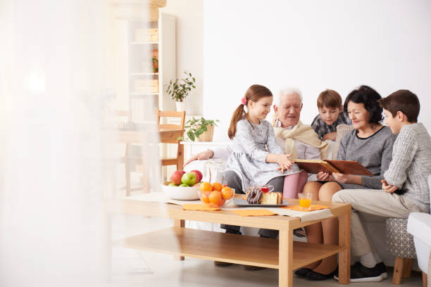 grandparents showing photo album to their grandchildren - family meeting stock photos and pictures