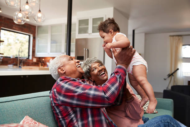 Grandparents Sitting On Sofa Playing With Baby Granddaughter At Home stock photo