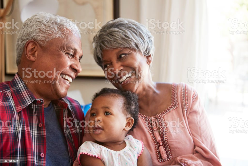 Grandparents Sitting On Sofa With Baby Granddaughter At Home stock photo
