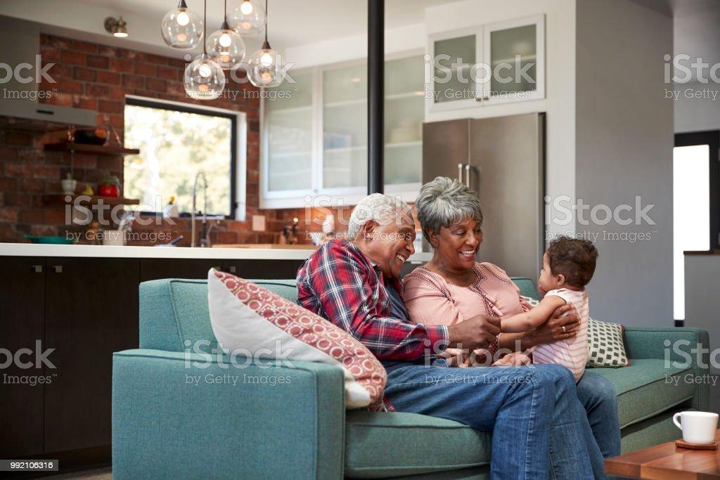 Großeltern mit Baby Enkelin zu Hause auf Sofa sitzen – Foto