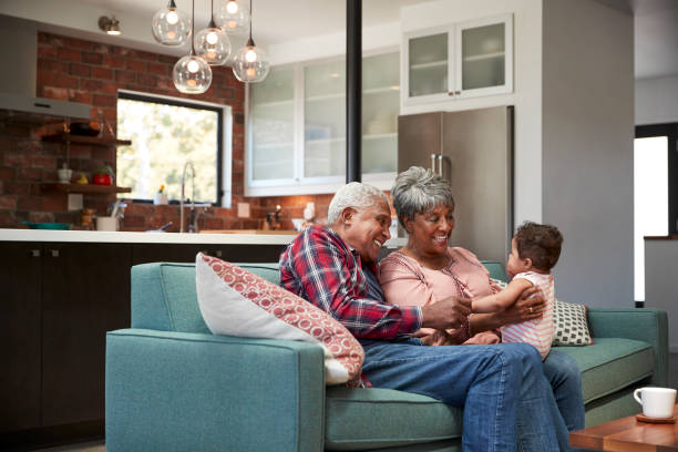 grandparents sitting on sofa with baby granddaughter at home - senior housing stock photos and pictures