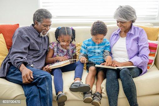 istock Grandparents sitting on sofa with two grandchildren, reading 623700470