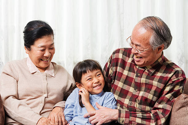 Grandparents smiling with their granddaughter stock photo