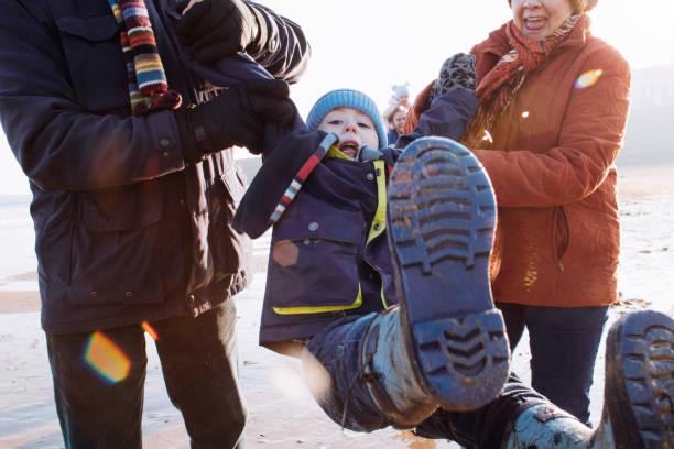 großeltern schwingen ihre enkel bei einem spaziergang am strand entlang - kinder winterstiefel stock-fotos und bilder
