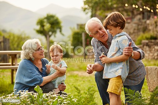 Grandparents talking to children. Family having leisure time in yard. They are wearing casuals.