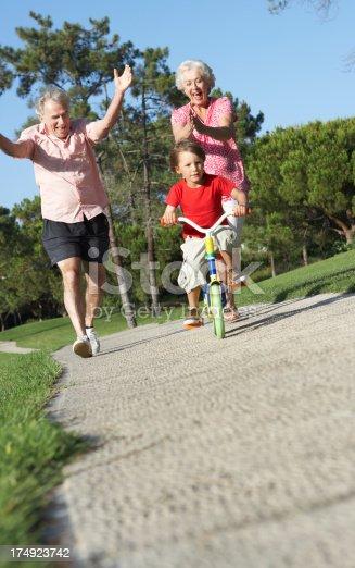 istock Grandparents Teaching Grandson To Ride Bike In Park 174923742