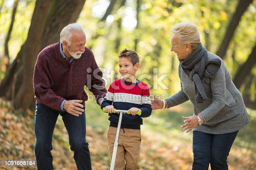 853720192 istock photo Grandparents Teaching Grandson To Ride Scooter In Park 1091658184