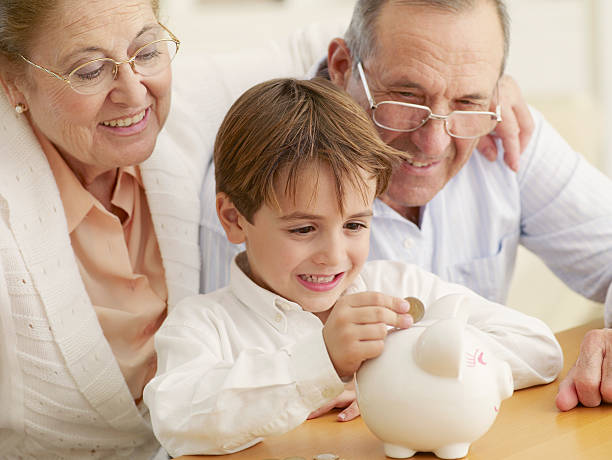 Grandparents teaching grandson to save money in a piggy bank stock photo