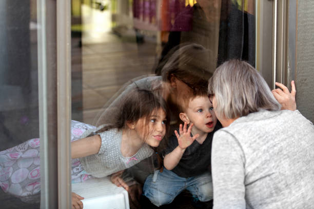 grootouders die kleinkinderen tijdens quarantaine door venster bezoeken - raam bezoek stockfoto's en -beelden