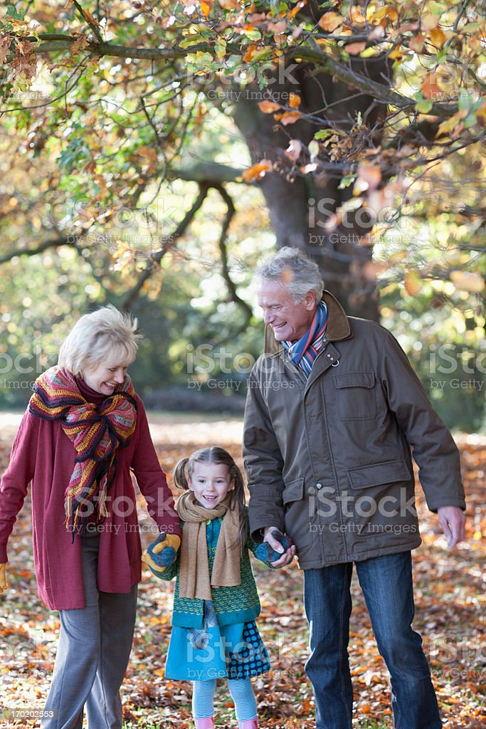 Grandparents walking in park with granddaughter royalty-free stock photo