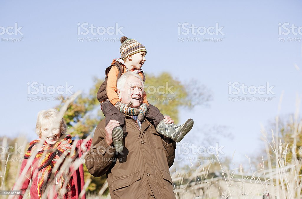 Grandparents walking outdoors with grandson royalty free stockfoto