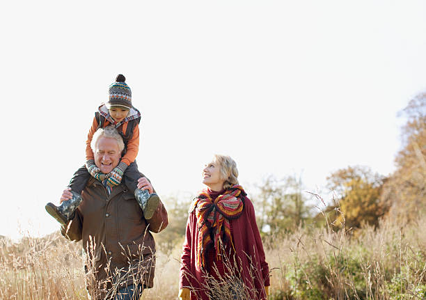 Grandparents walking outdoors with grandson stock photo