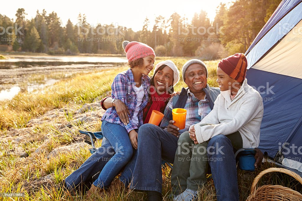 Grandparents With Children Camping By Lake stock photo