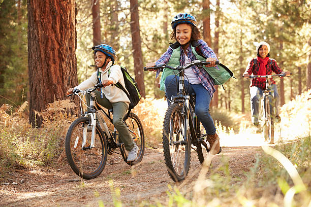 grandparents with children cycling through fall woodland - cycling stock photos and pictures