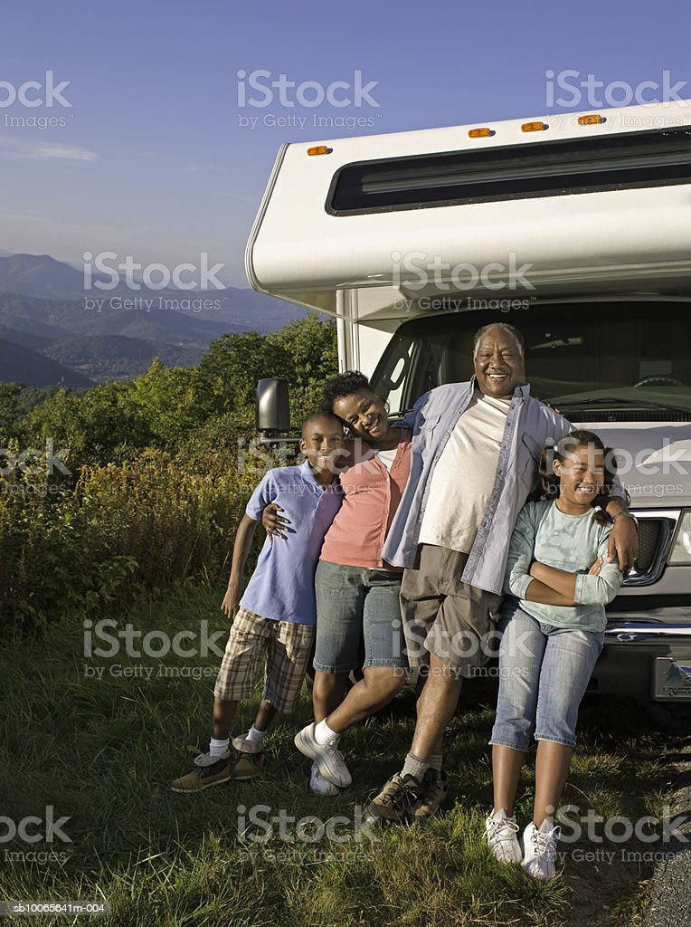 Grandparents with grand children (10-13) leaning against motorhome, smiling royalty-free stock photo