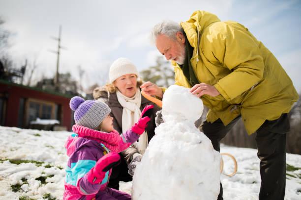 großeltern mit enkelkind haben winterspaß - schneemann bauen stock-fotos und bilder