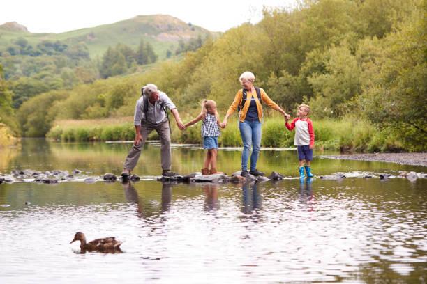 großeltern mit enkeln kreuzung fluß beim wandern im uk lake district - enkelin stock-fotos und bilder