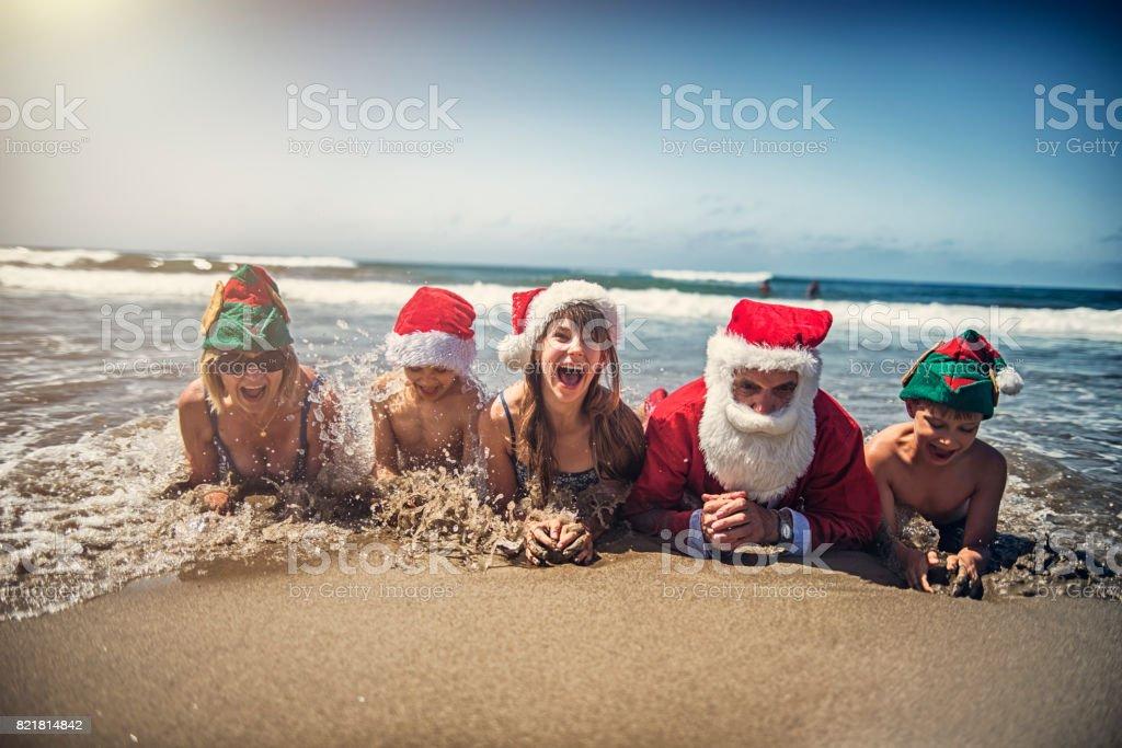 Grandparents with grandchildren having christmas on beach stock photo