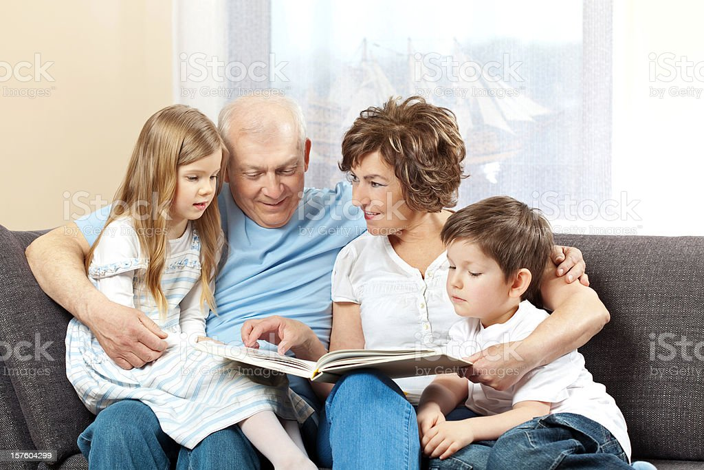 Grandparents with grandchildren reading book royalty-free stock photo