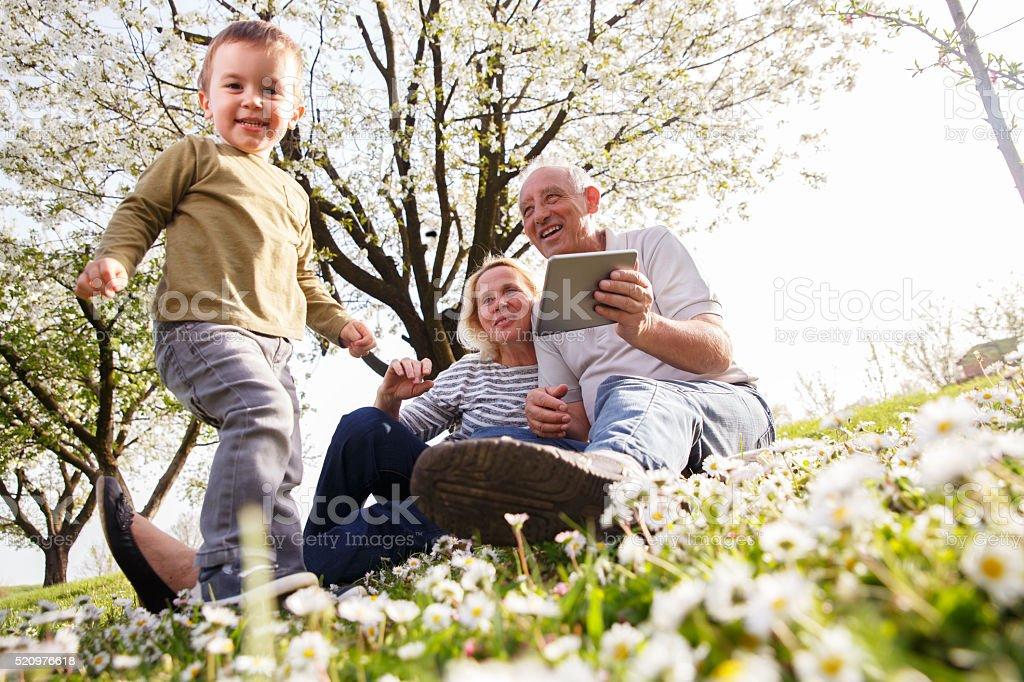 Abuelos y nieto disfruta de la soleada ciudad de día. - foto de stock