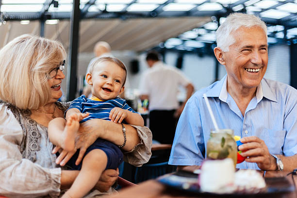 Grandparents With Their Grandson At Cafe stock photo