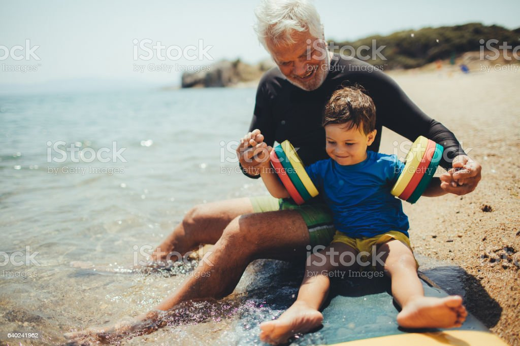 Grandpa's teaching me how to surf stock photo