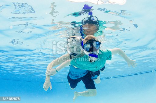 People swimming underwater on vacation with snorkels in beautiful blue water