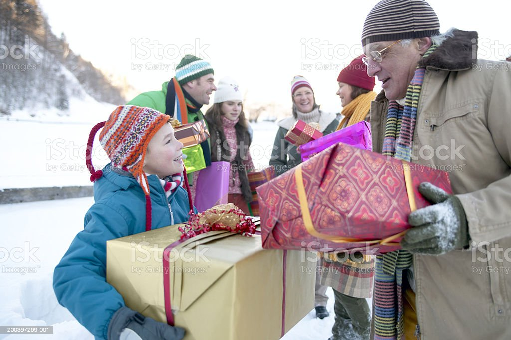 Grandson (8-10) and grandfather carrying presents in snow with family royalty-free stock photo