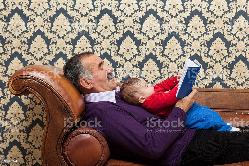 Enkel und Großvater liest ein Buch zusammen Lizenzfreies stock-foto