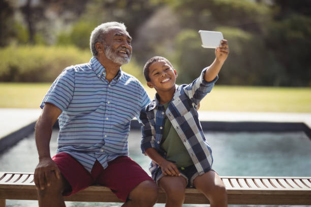 Grandson and grandfather taking selfie with mobile phone stock photo