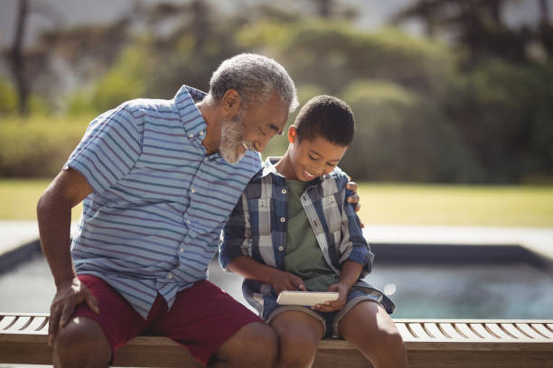 Grandson and grandfather using mobile phone stock photo